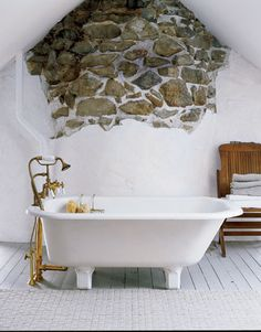The rough-hewn wall of this 1825 house was left exposed, to reference the home's history. Placing a vintage footed tub in front of the wall makes it a focal point. Painted floorboards and old-fashioned brass floor-mounted plumbing (try California Faucets) complete the authentic feeling.