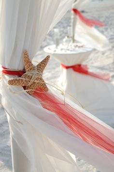 Bamboo canopy with white linen tied back with red tulle and a starfish tied with raffia. Our sand unity table is in the background tied with red tulle and topped off with sea shells and colored rocks