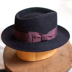 """From The Saucy Milliner: """"A bespoke beaver felt fedora in Black Cherry, featuring a 1940's hatting ribbon bow with kick, on the right side of the hat...the traditional side of the hat bows were worn on ladies' hats.  This black cherry beauty is for MOI!  :)  I made this with a 2.5"""" brim for a bit of dramatic flair and sculpted the tear drop crease.  A true hat for adventuring in."""""""