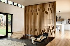 The sunken living room is separated from the dining space by a screen of wooden columns