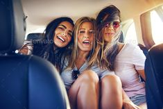 Three happy young women traveling on vacation by UberImages. Three happy young women traveling on vacation together sitting arm in arm in a car laughing and smiling viewed from t...