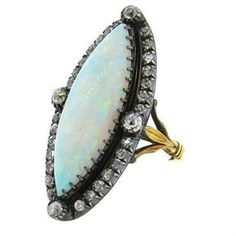 Antique ring in gold and silver top, featuring 26mm x 8.4mm white opal gemstone, surrounded with approx. 1.40ctw old mine cut diamonds DESIGNER: Not Signed MATERIAL: Silver, Gold GEMSTONE: Diamond, Op
