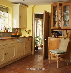 terracotta floor tile kitchen | terracotta floor tiles in yellow country kitchen with cane chair in ...