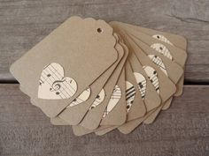handmade gift tags ... clean and simpl;e ... kraft ... hearts punched from sheet music ... like the placement of the treble clef on the top one ... nice idea for simple valentine packages ...