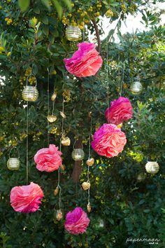 Rincón con flores colgantes de papel, guirnalda de luces y farolillos. http://www.papermoonandco.com/