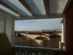 Cerramiento de terraza mediante instalación de  pérgola de hierro, techo y pared lateral de cristal fijos.