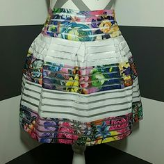 """🆕 Gorgeous floral print skirt *MORE SIZES* BRAND NEW WITH TAG  Gorgeous floral print with white stripes skirt. Rows of floral elastic, white elastic and clear fabric make this skirt a true statement maker.  White lining Size small Total length approximately 15.5"""" zip up in back  Material 80% polyester 20% elastic (skirt is semi stretchy) Size small  *Juniors or petite fit in my opinion*  *AVAILABLE IN SMALL or LARGE* Skirts"""