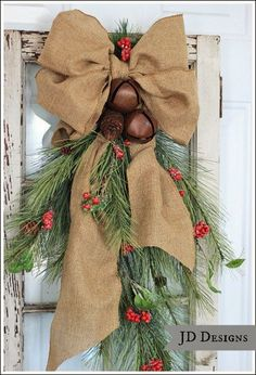 JD Designs - Cedar Christmas door swag with rustic bells, berries, and a pretty bow.