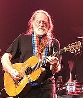 A man with long white hair and white beard playing a guitar. He wears a black t-shirt, which is crossed by the red, white and blue strap of ...
