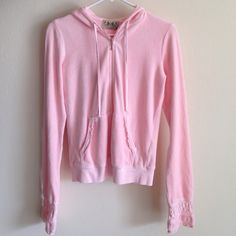 Juicy Couture Hoodie Juicy Couture velour hoodie that's a pinky peach color. Has pretty eyelet around the bottom of the sleeves and pockets . The sleeves are long on this and probably need to be cuffed. I wore this once, Great condition!!'  Juicy Couture Tops Sweatshirts & Hoodies