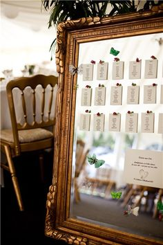 The table plan was printed onto textured paper and stuck onto an ornate mirror with tiny silk rose buds and butterflies for decoration.