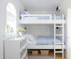 Outfitted with a charming pair of queen-size bunk beds, each with its own television, this guest bedroom keeps things casual. White furnishings, accented with gray and blue, give the gulfside cottage space carefree spirit./