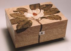 Magnolia Box A large magnolia design jewellery box in burr ash with mother of pearl escutcheon. A fine example of contemporary marquetry that showcases the depth that can be achieved using fine sand shading and the technically correct continuous flow of the design from the top over the sides of the box. Size: 240mm x 147mm x 76mm