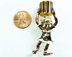 SoVintageous is offering this highly collectible Charles F. Worth brooch depicting an enamel and goldtone African Tribal figure of a woman carrying a Bakelite drum (or pot) on her head.  This wonderfu