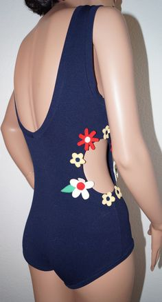 Vintage 1960s mod one piece swimsuit with round peek-a-boo cutout on left side surrounded by floral appliques in yellow, red and white running