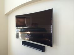 Curved flat panel TV mounted on a wall with Sonos PLAYBAR home theater soundbar system mounted beneath.