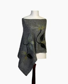 Gray poncho, capelet, hand knitted from yarn mohair and acrylic, with felted flower applique on it. $90.00, via Etsy.