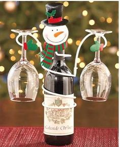 Celebrate the spirit of the season with this Holiday Wine Bottle & Glass Holder. Its spiral body fits snugly around a standard wine bottle, while its two arms hold your wine glasses. Cheerful holiday character adds fun detail to the useful piece. Wine Bottle Glass Holder, Wine Bottle Crafts, Glass Holders, Beer Bottles, Christmas Wine Glasses, Christmas Wine Bottles, Wine Decor, Wine Gifts, A Table