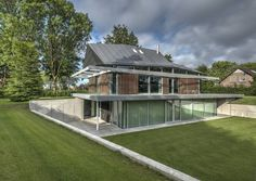 This home resonates individuality around every corner. The designers and architects have used industrial materials and elements to create a homely vibe. We can see from its construction just how well the metal, wood and glass work together. The well-manicured lawn also sparkles along with the glass walls and robust concrete and wooden facade.Houses by Coenen Sättele Architecten.