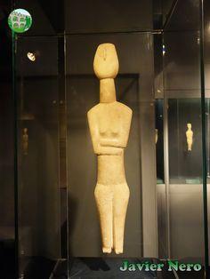 """Las piernas cortas y robustas en relación con el tronco no tienen rodillas y terminan en pies rudimentarios. Con toda probabilidad, las piernas se habían roto al nivel de las rodillas, donde el artista talló los dedos de los pies. Las figuras son uno de los raros ejemplos de remodelación en el arte de las Cícladas. Tipo canónico. Spedos variedad. Atribuido al """"Maestro de Copenhague"""". II periodo. Fase Syros (2800-2300 a.C.) Museo del Arte Cicládico, Atenas."""