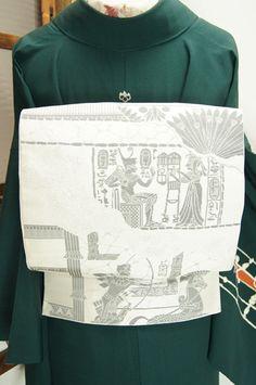 パールホワイトとシルバーのバイカラーで織り出された古代エジプトのパピルスの絵巻物を写しとったような絵図がロマンをさそう洒落袋帯です。