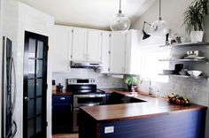 Fresh, eclectic kitchen with dark lower cabinets and tile up to the ceiling