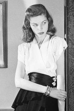 missavagardner:  Lauren Bacall wearing an Adele Simpson tango crepe with peplum attached to the white surplice top, and black satin swathing her slim waist, 1945.