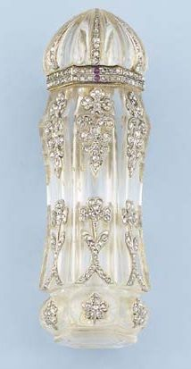 A BELLE EPOQUE ROCK CRYSTAL AND DIAMOND SCENT BOTTLE, BY BOUCHERON. The rock crystal hexagonal bottle with old-cut diamond floral detail to the fluted dome lid, opening to reveal a faceted rock crystal stopper, circa 1905, 7.3 cm. high. Signed Boucheron Paris. #BelleÉpoque #Boucheron #ScentBottle