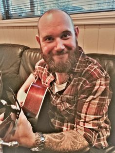 Bald, but still smiling! Tattoos, plaided shirt and a brown beard!