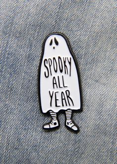 """Black and white """"Spooky All Year"""" enamel pin of a ghost kid. A cute accessory for Halloween fashion."""