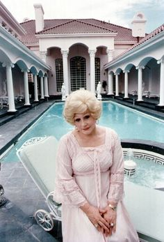 She looks like a drag queen! Or Baby Jane Hudson! Mary Kay Ash by the pool of her pink mansion