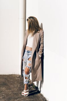 Mandy Shadforth is wearing a beige coat from Theory, distressed denim jeans from One Teaspoon and slides from TopShop
