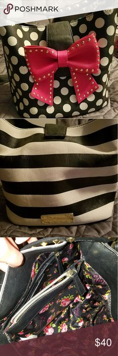 Betsey Johnson purse Black and white. One side is b/w with polka dots the other is b/w stripes. The studded bow on the front is red. Inside in great condition! Straps in good condition. The polka dots along the top and a few on the bottom have some rub marks. Really sweet purse! Got me a lot of compliments! Betsey Johnson Bags Shoulder Bags