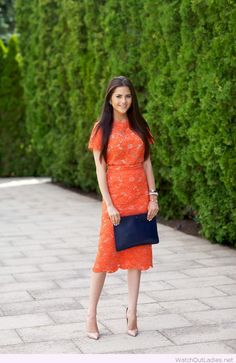 Orange lace dress, nude pumps and navy bag