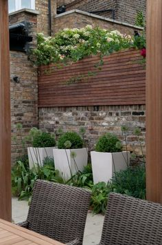 irecyclart: Little Chelsea courtyard garden Access was restricted through the immaculately furnished house but this little courtyard doesn't look stinted in any way.  The back wall height has been raised with a timber planting box matching the height of the other walls & adding privacy. The garden materials are old brick walls, sawn timber & decking, and lush groundcover plantings in the beds and planters. Seating, dining table, heating, & an integrated kitchen with BBQ fit neatly.