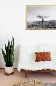plaide fourrure blanche et coussin marron sur un canape blanc