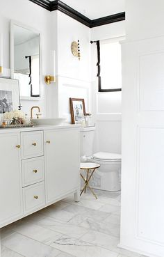 white bathroom with gold / brass accents