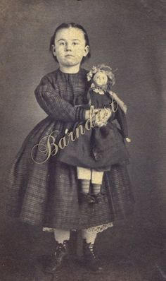 Little Girl Holds Lookalike Crazy Alice Wax Over Mache Doll