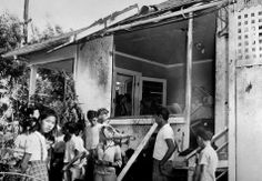 A small crowd inspects the damage, both inside and outside, after a Japanese bomb hit the residence of Paul Goo during the raid on Honolulu Dec. 7, 1941.