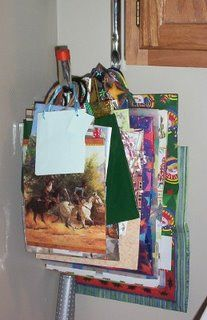 This is a great way to organize your gift bags. (Bags you are saving from birthdays to reuse for gifting, a stack of Christmas gift bags) Likemerchantships suggest using a large ladder hook and hanging it up in your storage room or wrapping area. Makes it easy to see what you have and search through the collection for the one you need.