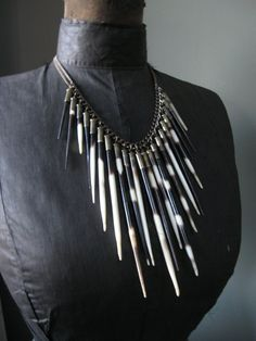 Amazing African porcupine quill tips are capped with upcycled spent brass bullet casings (22s to be exact). The quills are all different lengths and are suspended from oxidized vintage brass chains to form the perfect necklace for all your nomadic tendencies. The quills have had their barbs removed, and the tips have been sanded smooth so they wont accidentally poke you.  Necklace measures 18 (Landing the quills right at the bust-line on an average sized woman). Need a shorter length? No…