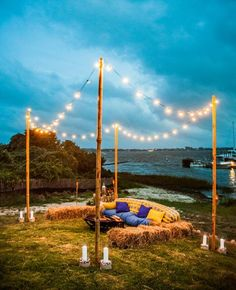 An inviting evening lakeside wedding lounge with hay bale seating and string lighting. Joshua Zuckerman Photography via The Knot #summerwedding #weddinglounge