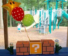 Super Mario Bros centerpiece with bricks, question box, star balloons and warp pipes