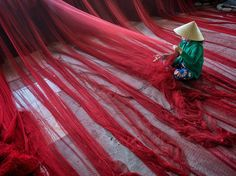 In My Tho, Vietnam, an expanse of fishing net is checked for damage in this National Geographic Photo of the Day.