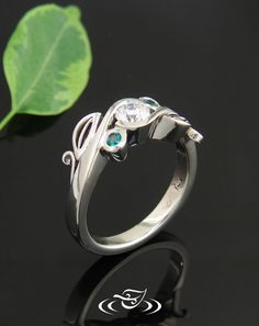 14kt white gold wrap style ring with diamond and emeralds. Leaf accents on sides.