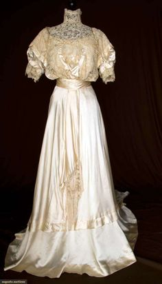 SILK SATIN & LACE WEDDING GOWN,1912-1914. Lot 300. Nov.10, 2010, St. Pauls -  NYC. Brussels lace & Pt. de Gaz h.m. lace bodice, trained cream silk skirt, draped side panels, wide self fabric waist sash, low CF knotted silk fringe w/ double garland of strung silk looped balls, American labeled petersham, (ivory silk illusion fabric under lace bodice damaged, few holes in net area of Pt de Gaz cartouche) very good. Price Realized: $120.00. Category: Womens. Era: 1890-1920. Condition: Excellent