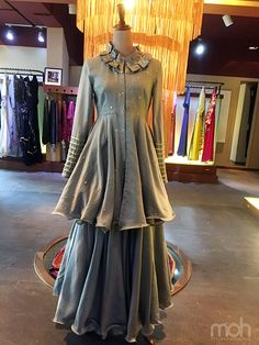 Enhance your classy look in this Grey Chanderi Peplum Top with pleat embellished collar and flared skirt; customized for a client. Get your dress customized for any occasion at moh! to get this at its reasonable rate log on to prasang. Pakistani Outfits, Indian Outfits, Pakistani Clothing, Indian Designer Outfits, Designer Dresses, Stylish Dresses, Fashion Dresses, Choli Dress, Indian Gowns Dresses
