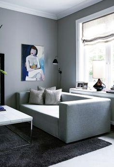De stribede puder – i den grå, dybe sofa fra Othilia Decor – er designet af Jasper Conran. Maleriet på væggen er malet af Maries mor, Lene Sand. Sofabordet er bestilt efter mål hos italienske Minotti, hvor gulvtæppet også er fra. Lampen på væggen er fra Bestlite, og lampen i vindueskarmen er fra Rue Verte.