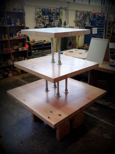 This three-tiered merchandizing table was designed and installed by Gabe for  The reclaimed lumber is supported by four columns on the bottom shelf and then two columns on the top shelf. This...