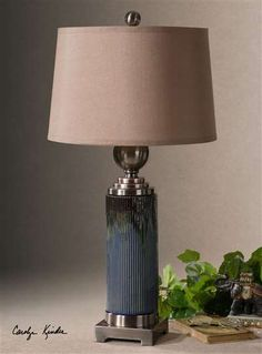 Montagano Ribbed Table Lamp Ribbed Ceramic Base Finished In A Distressed Blue Glaze With A Dark Bronze Drip And Brushed Antiqued Bronze Metal Details. The Round, Slightly Tapered, Hardback Shade Is Silken Bronze Linen Fabric.